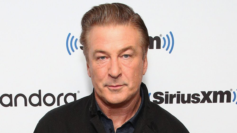 Alec Baldwin with a slight smile