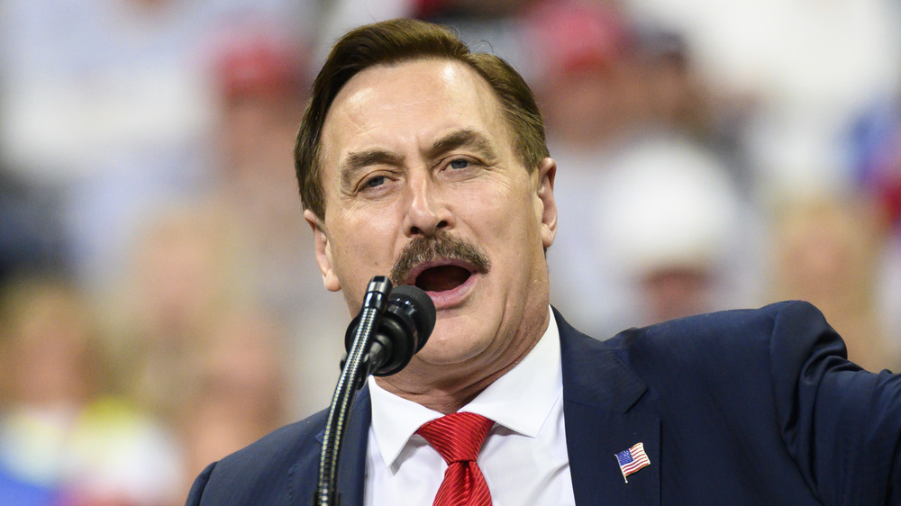 Mike Lindell, speaking at a podium, mouth open, in a suit