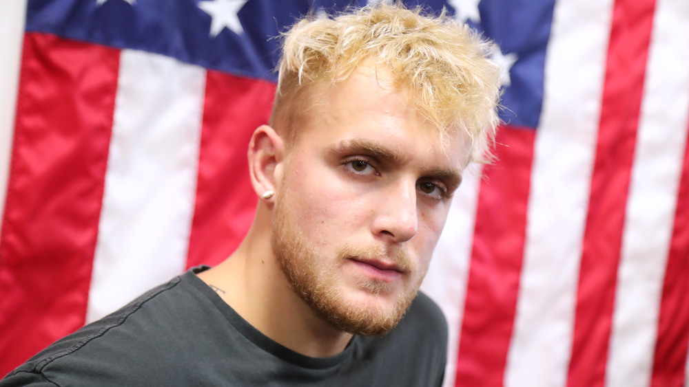 Jake Paul looking serious in front of an American Flag