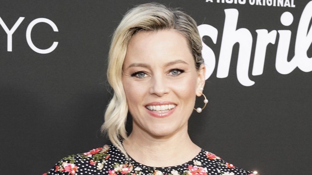 Elizabeth Banks a black, white-polka dotted, floral dress, posing with a smile at an event