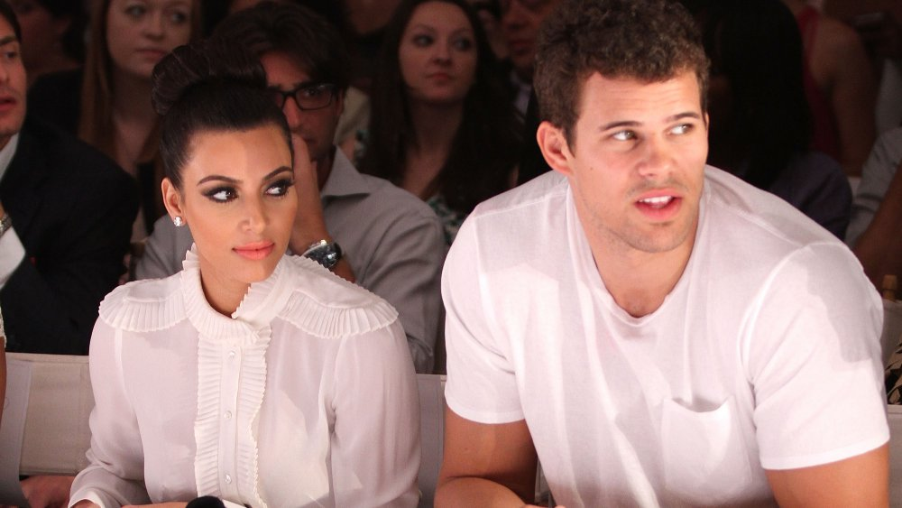 Kim Kardashian and Kris Humphries sitting next to each other
