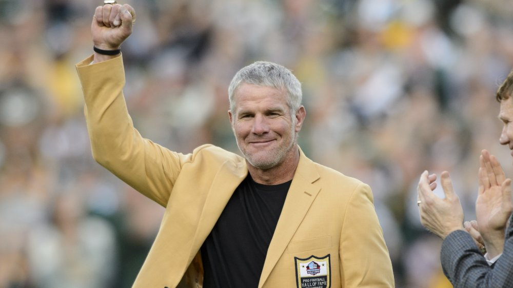 Brett Favre in a yellow Hall of Fame blazer, posing with his fist up in the air at a game