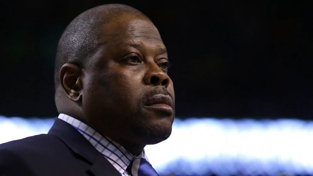 Patrick Ewing in a blue blazer and checkered shirt, looking off to the side with a serious expression