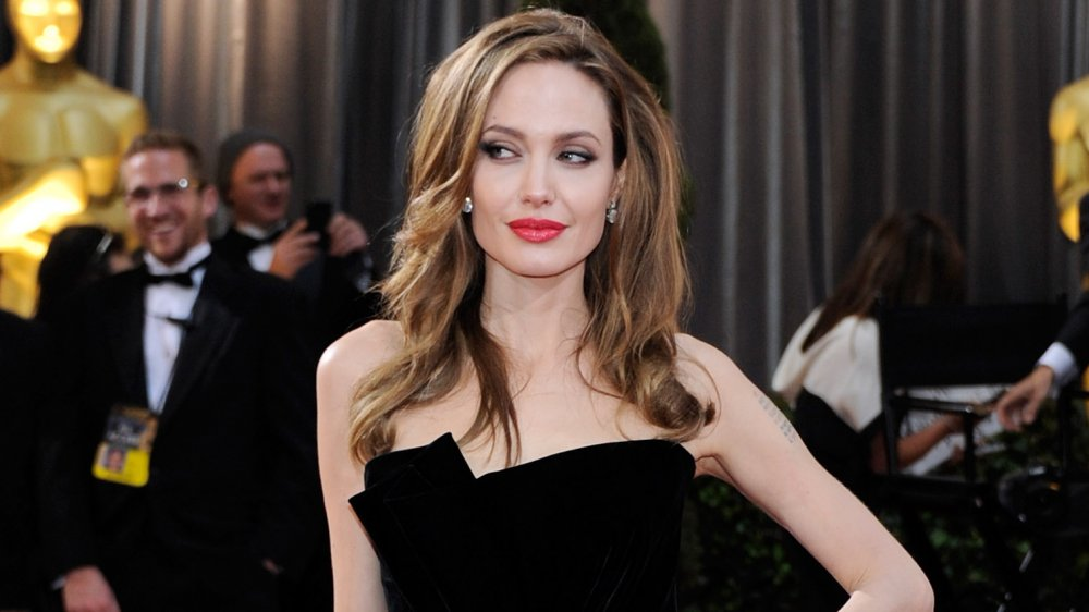 Angelina Jolie posing in a black dress at the Oscars, looking off to the side