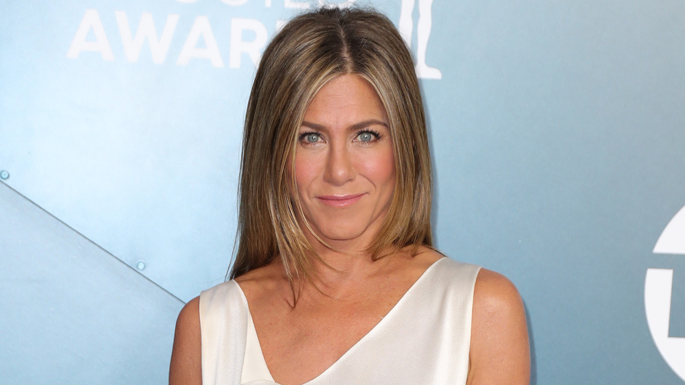 Jennifer Aniston in a white dress, posing at an awards show with a neutral expression