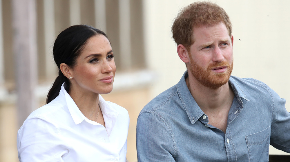 Meghan Markle in white sits next to Prince Harry in a jean shirt as they look out pensively at an event