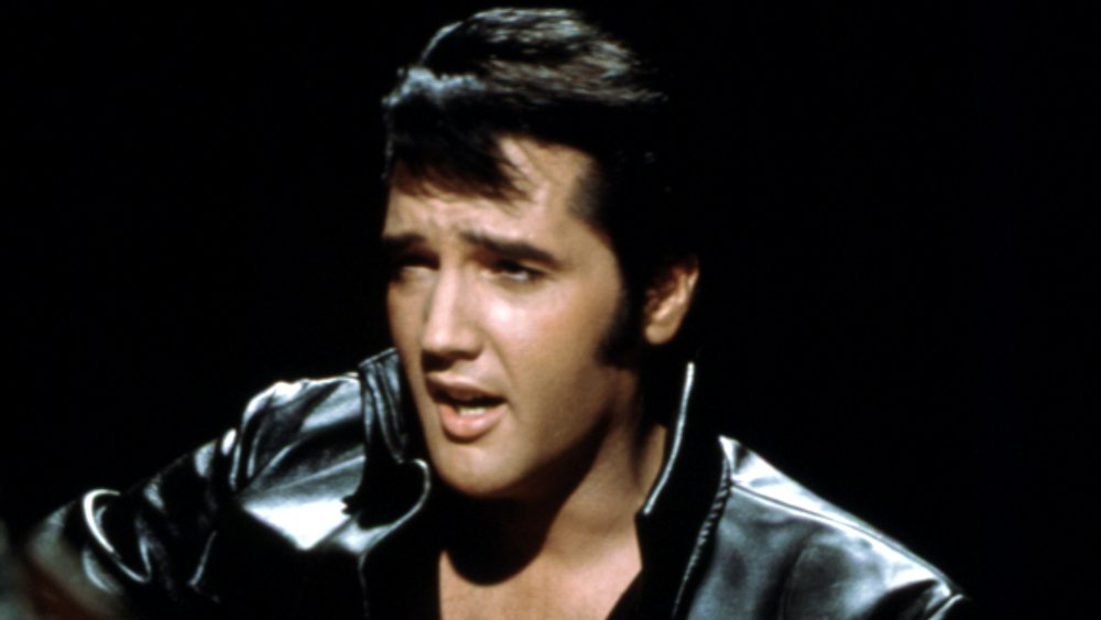 Elvis Presley playing guitar and wearing a black leather jacket