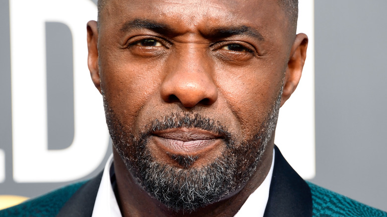 Idris Elba staring with a serious expression
