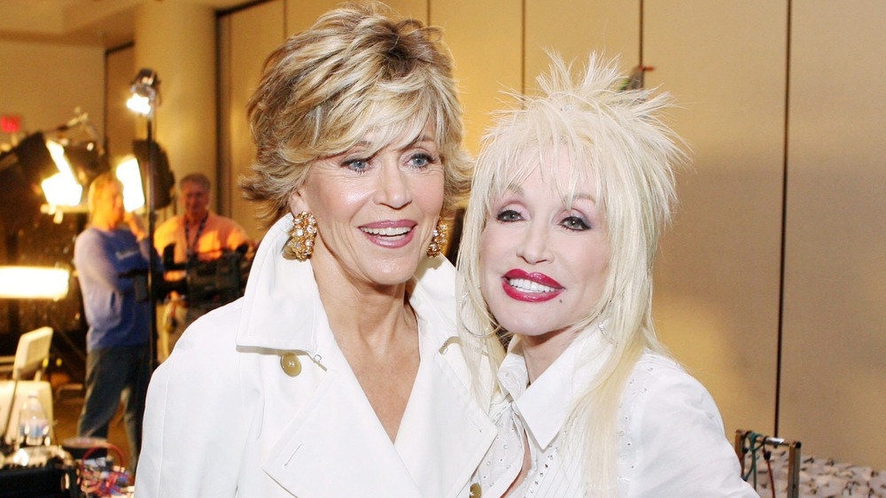 Dolly Parton and Jane Fonda smiling while wearing white