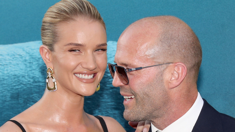 Rosie Huntington-Whiteley and Jason Statham laughing together on the red carpet