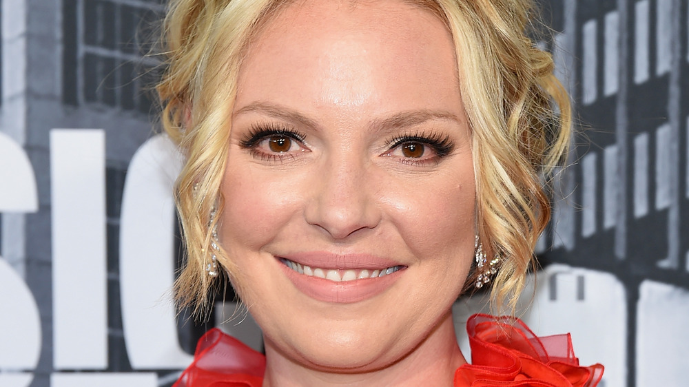 Katherine Heigl smiles while posing at an event