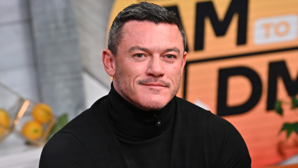 Luke Evans sitting happily at an event