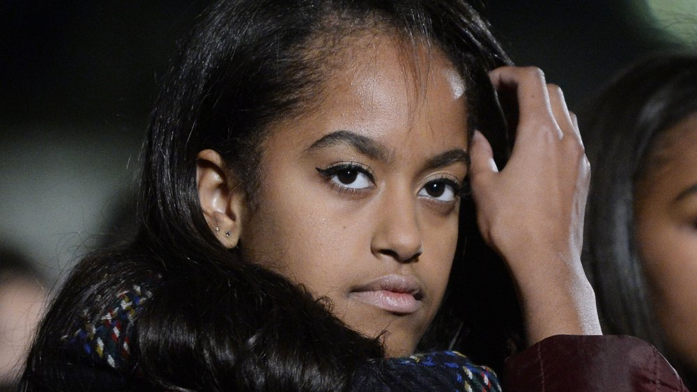 Malia Obama with a neutral expression, fixing her hair