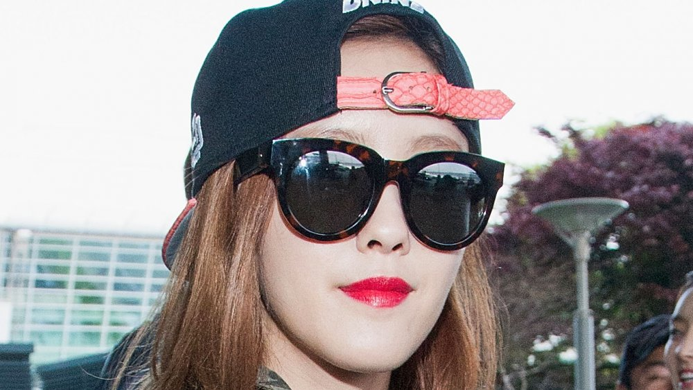 Hyomin of T-ARA in a black backwards hat and sunglasses