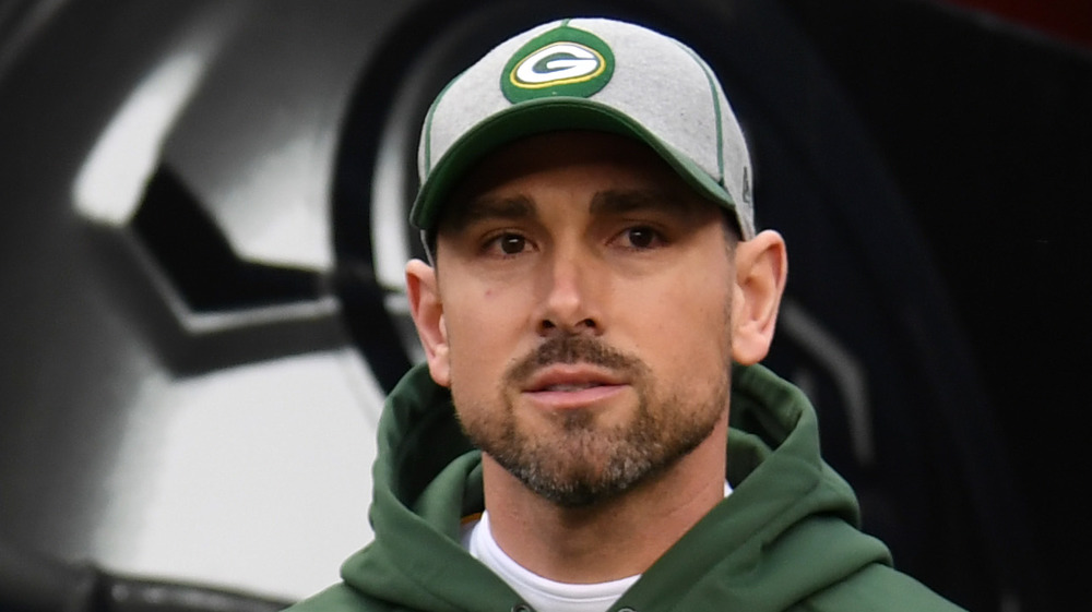 Matt LaFleur wears a Green Bay Packer's hat while walking in the club's tunnel