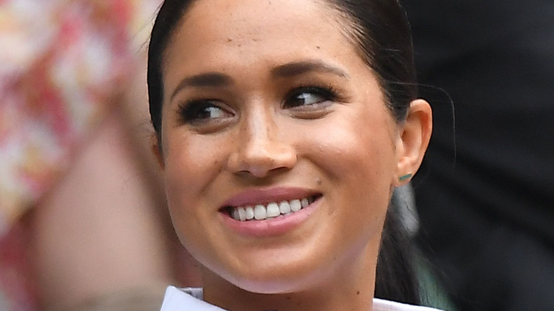 Meghan Markle grinning and looking to her side