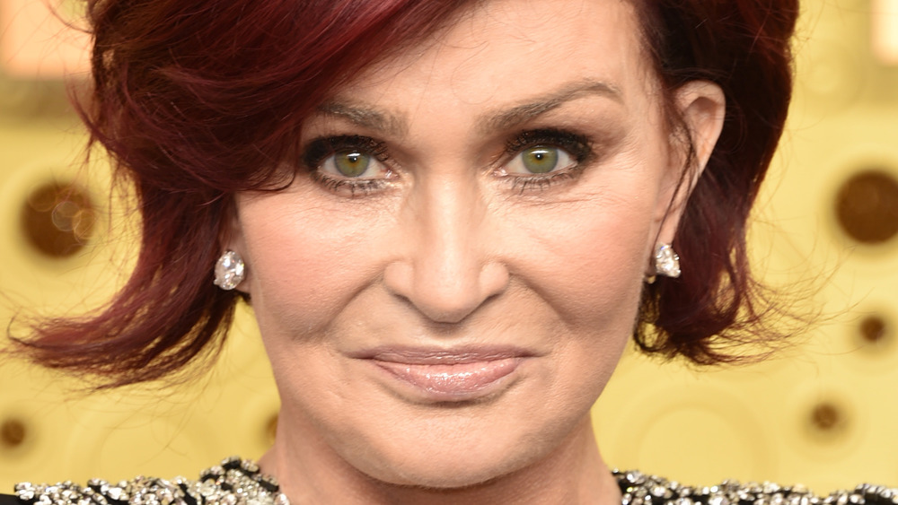 Sharon Osbourne stares into the camera while posing on the red carpet