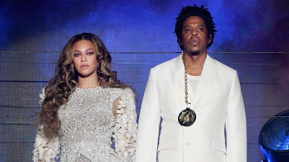 Beyonce and Jay-Z performing on stage together, both looking serious and looking out into the crowd