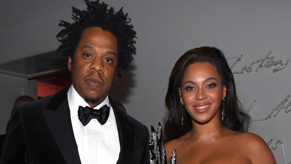 Jay-Z looking serious in a back suit and bow-tie, Beyonce smiling in a black bejeweled dress