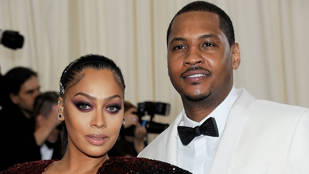 La La Anthony in a maroon sparkly dress, Carmelo Anthony in a white suit with black bow-tie