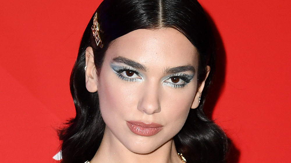 Dua Lipa gazing at the camera on the red carpet