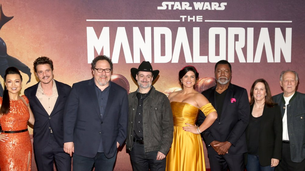 The Mandalorian cast in front of promo poster