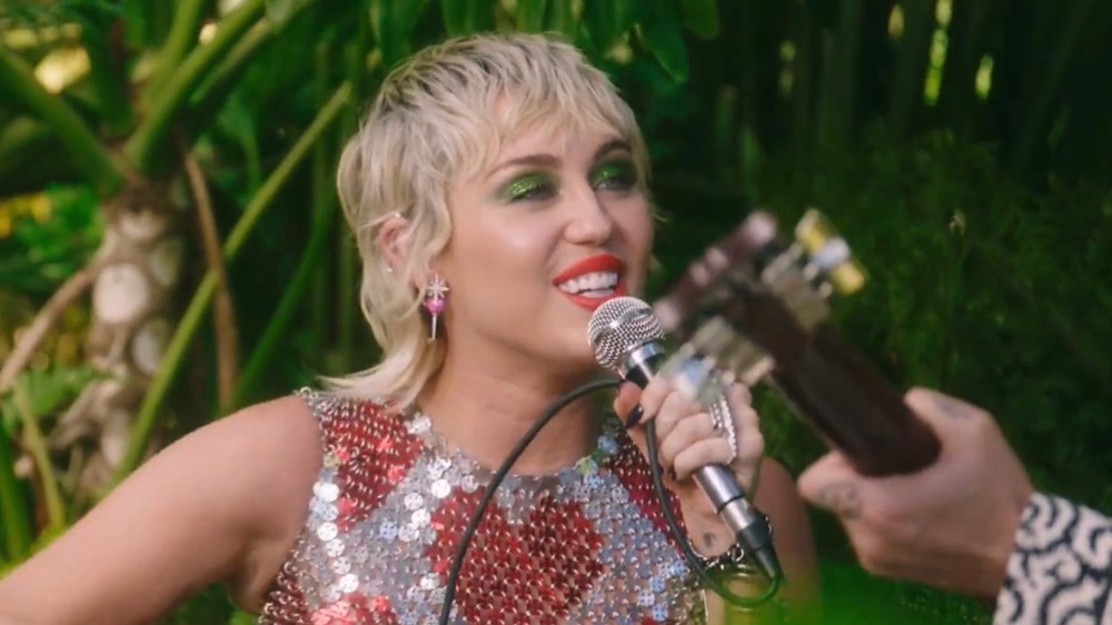 Miley Cyrus sings outdoors into a microphone with a guitarist's hand in view