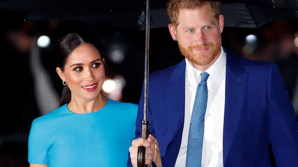 Meghan Markle and Prince Harry stands under an umbrella at an event