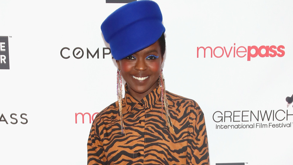 Lauryn Hill smiling in blue hat and tiger print blouse