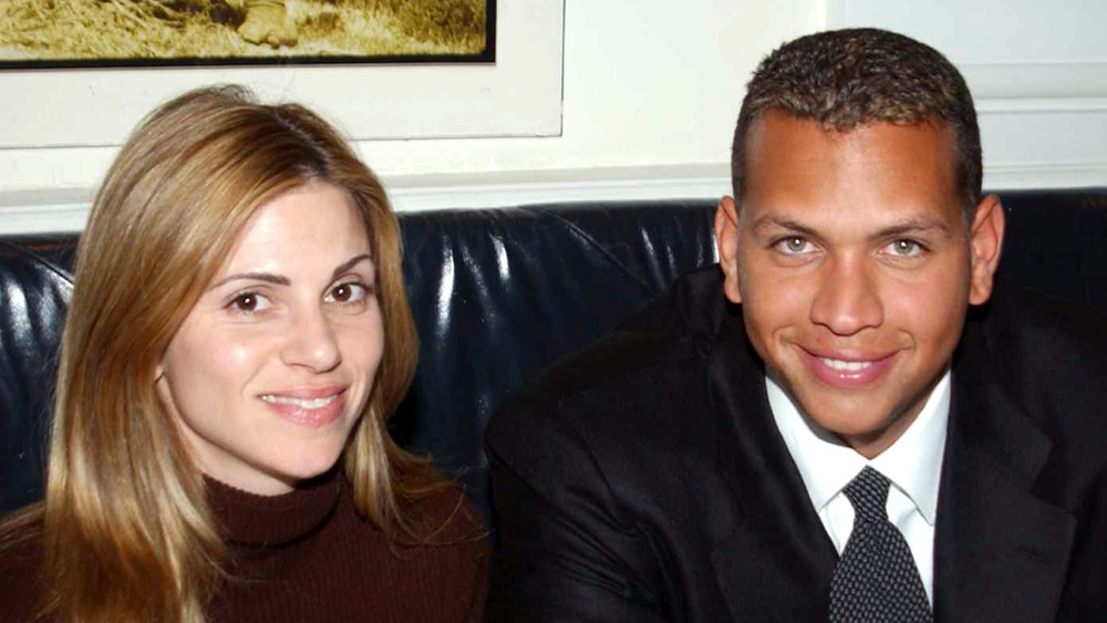 Cynthia Scurtis and Alex Rodriguez seated on a couch, smiling