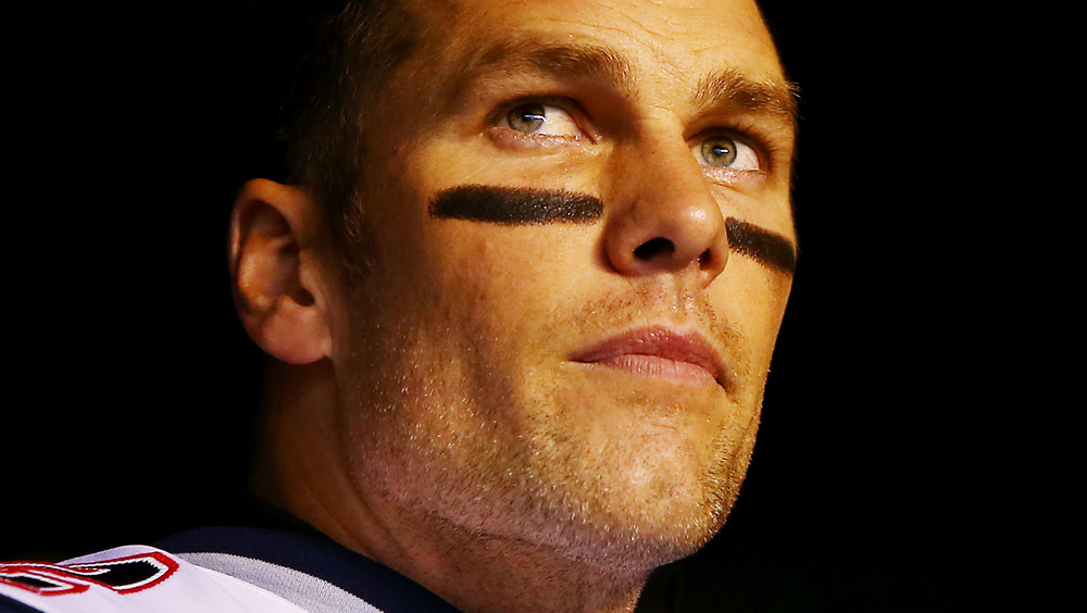Tom Brady wearing grease paint, looking serious