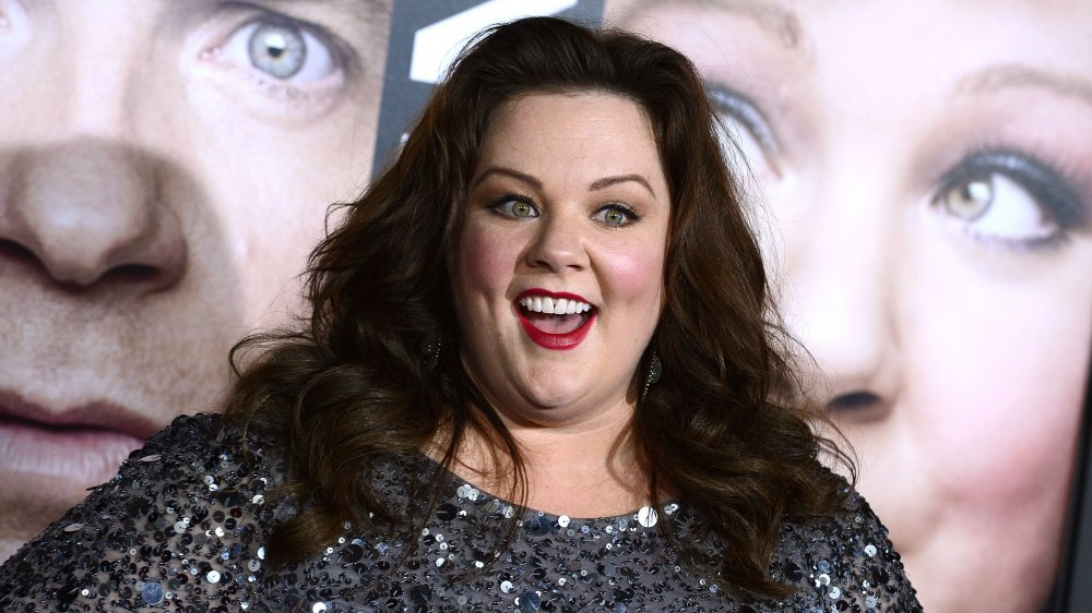 Melissa McCarthy in a black, sequined dress, smiling big at The Thief premiere