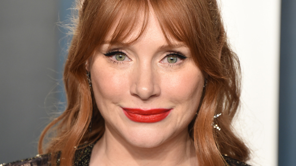 Bryce Dallas Howard wears red lipstick and smiles at an event