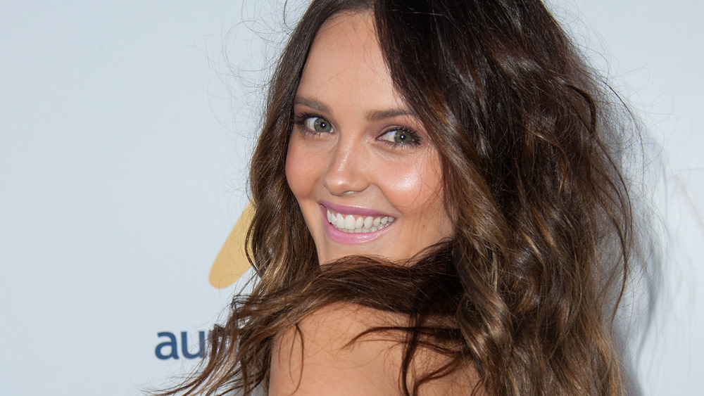 Rebecca Breeds smiles for a photo on the red carpet