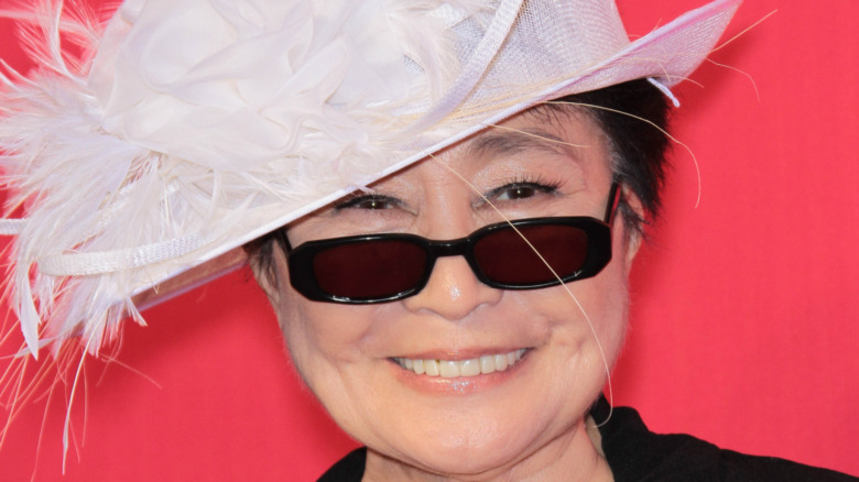 Yoko Ono smiling in sunglasses and a feathered hat