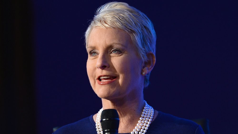 Cindy McCain in a blue dress and pearl necklace, speaking into a mic