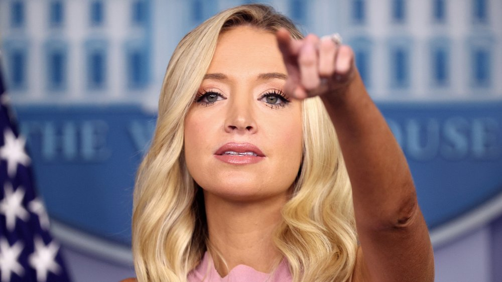 Kayleigh McEnany in a light pink dress, pointing to a reporter during a White House press briefing