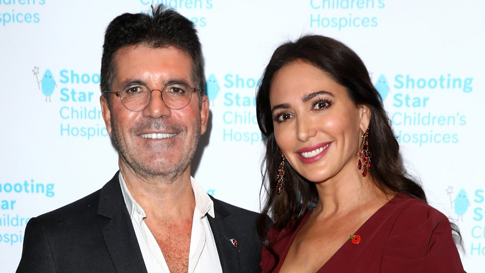 Simon Cowell and Lauren Silverman, smiling while posing arm in arm