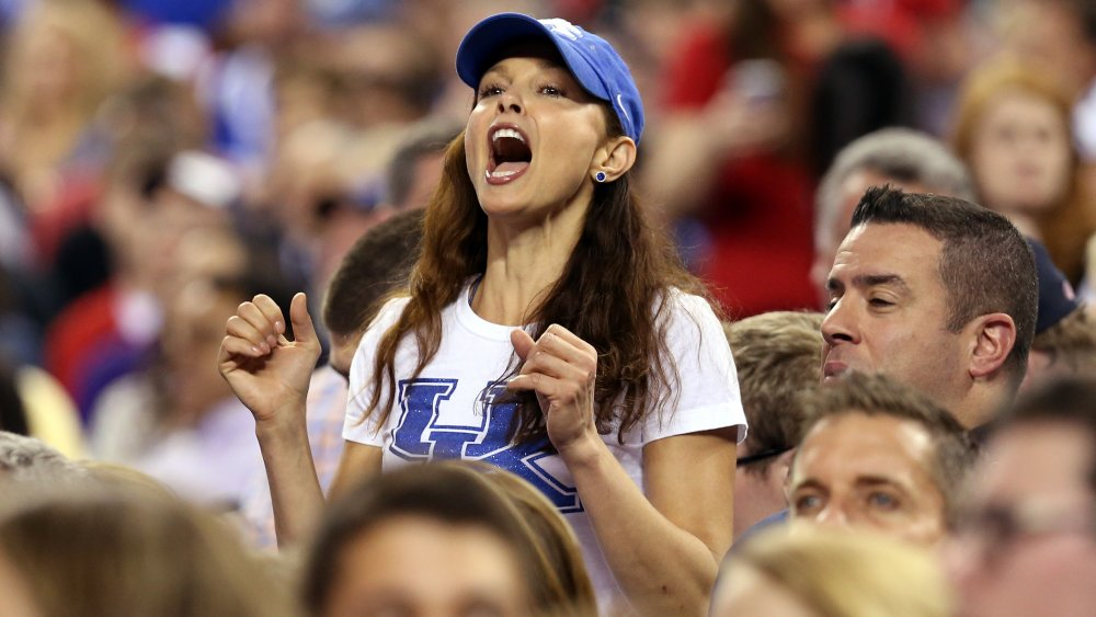 Ashley Judd in a blue-and-white t-shirt and hat, cheering at a sports event