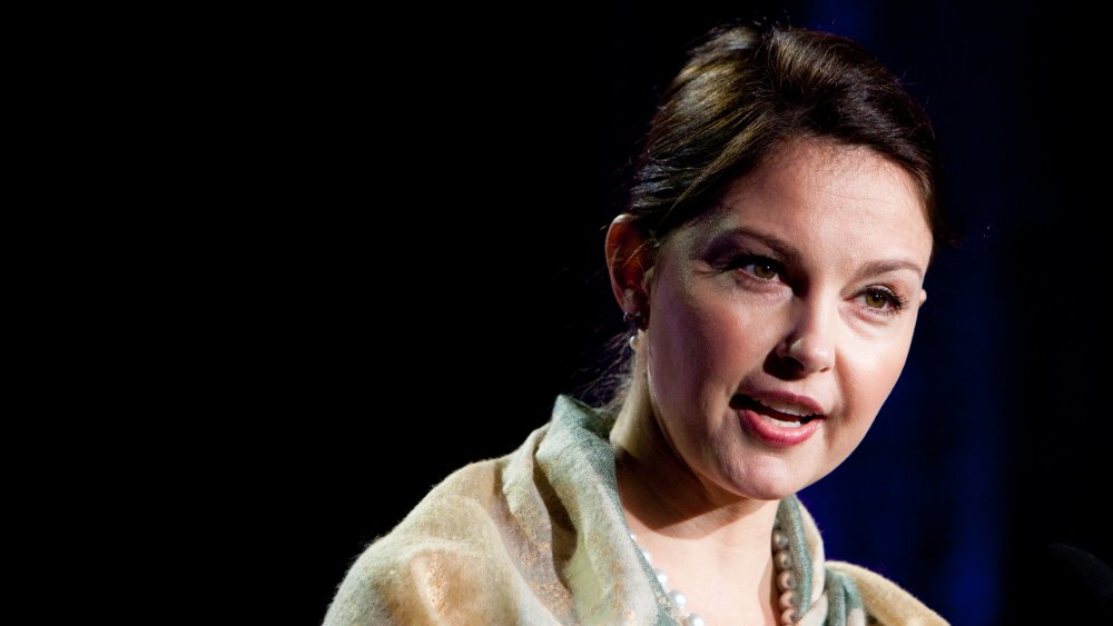Ashley Judd in a light, multi-colored shall and white pearl necklace, speaking at an event