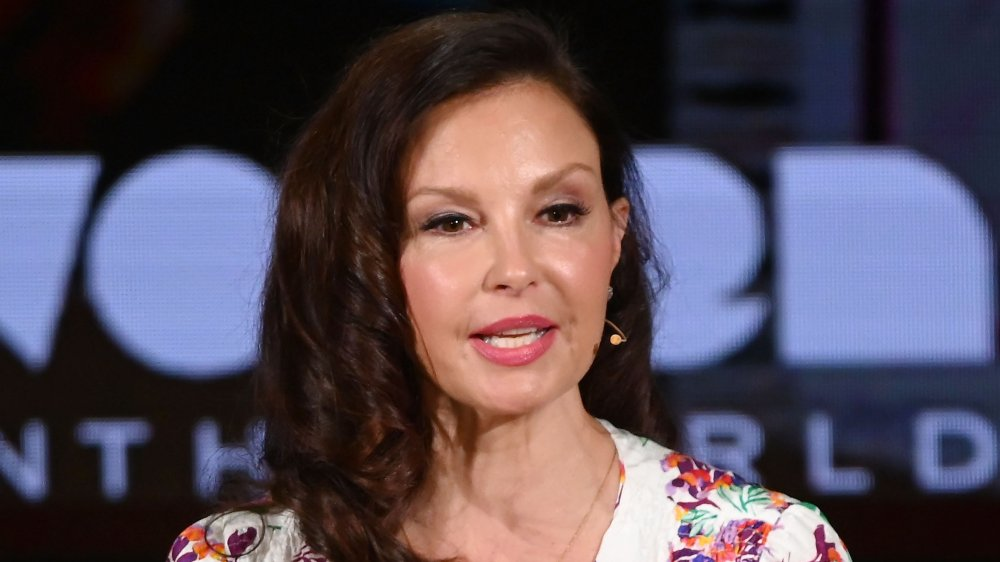 Ashley Judd in a white floral-printed dress, speaking with her hands at an event