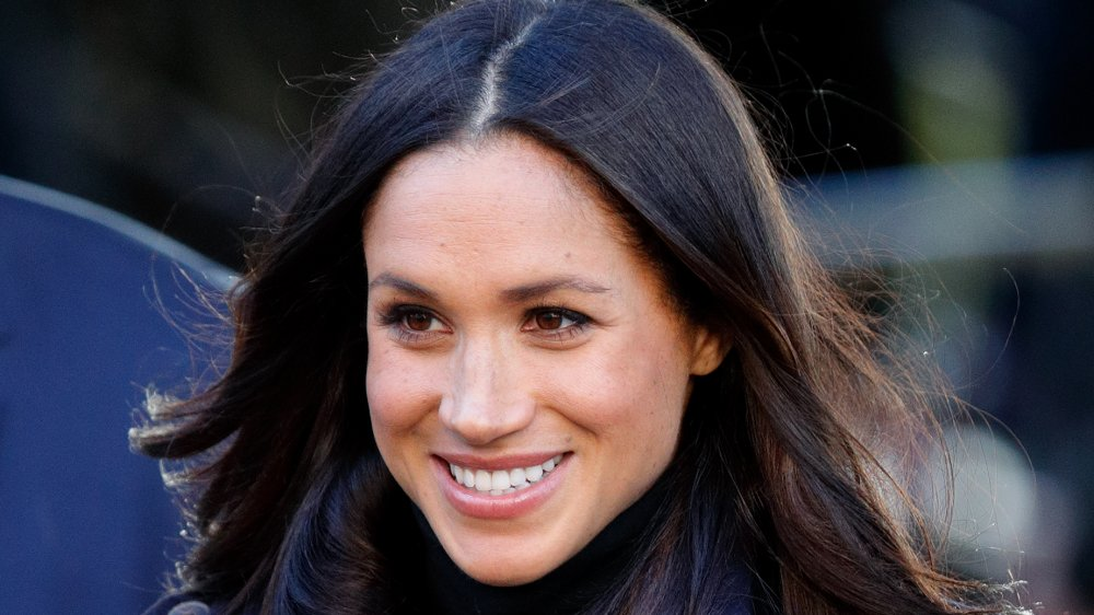 Meghan Markle smiling, head off to side