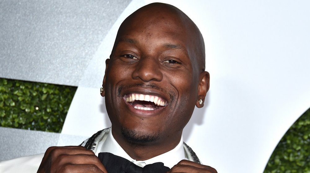 Tyrese Gibson in a white suit, smiling big as he adjusts his black bow-tie on the red carpet