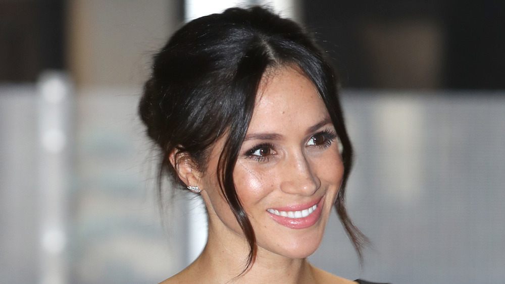 Meghan Markle smiling with her hair pinned up