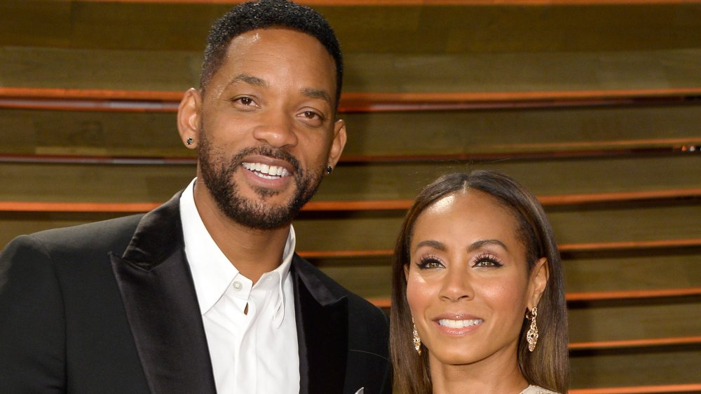 Will Smith in a black blazer and white shirt with no tie, Jada Pinkett Smith in a white-and-gold dress, both smiling