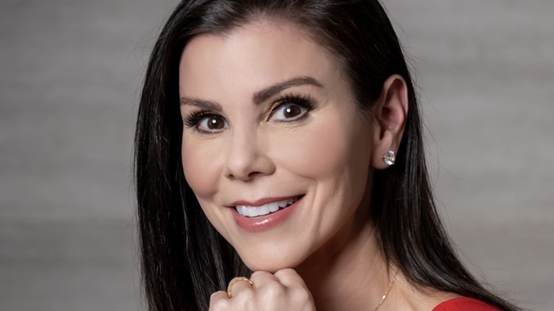 Heather Dubrow smiling, resting her chin on her fist