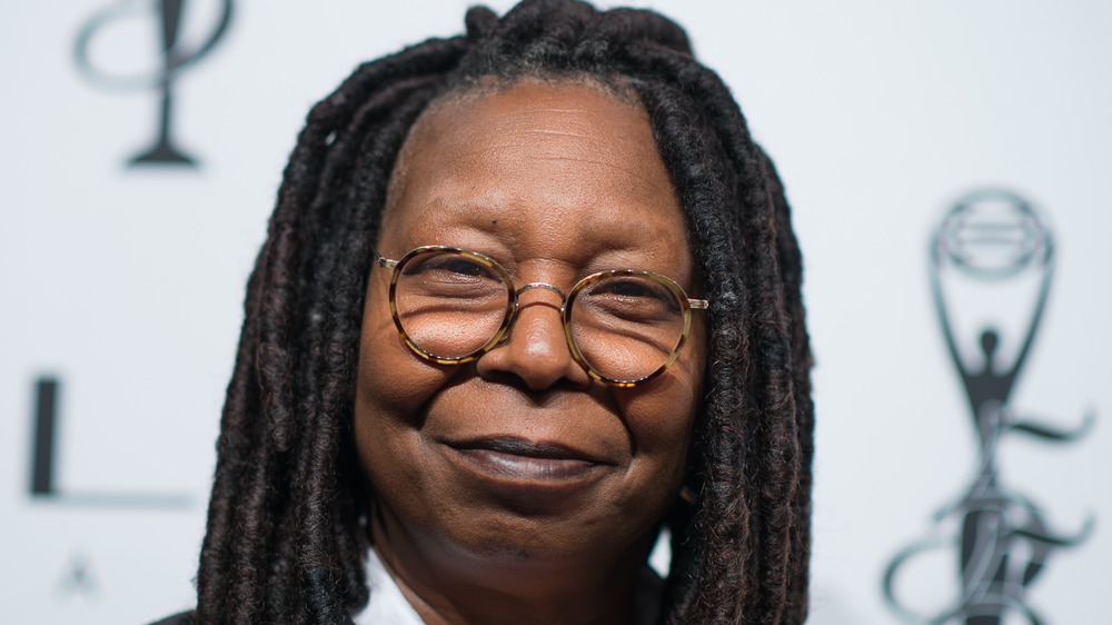 Whoopi Goldberg grins on the red carpet
